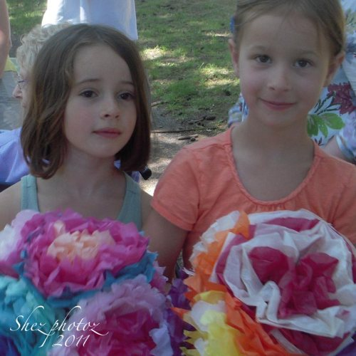 Two pretty girls help clean up and get to keep the giant and very colorful paper flowers