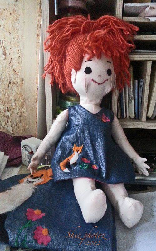 The doll has a dress that matches the young girl's dress.