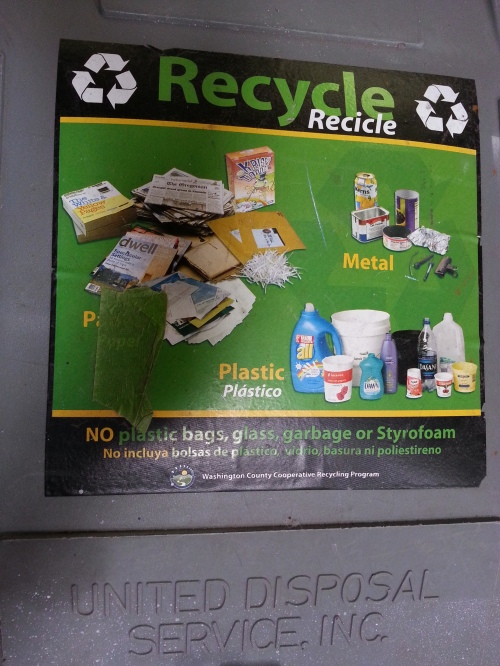 Bright green poster attached to the lid of a recycle container.
